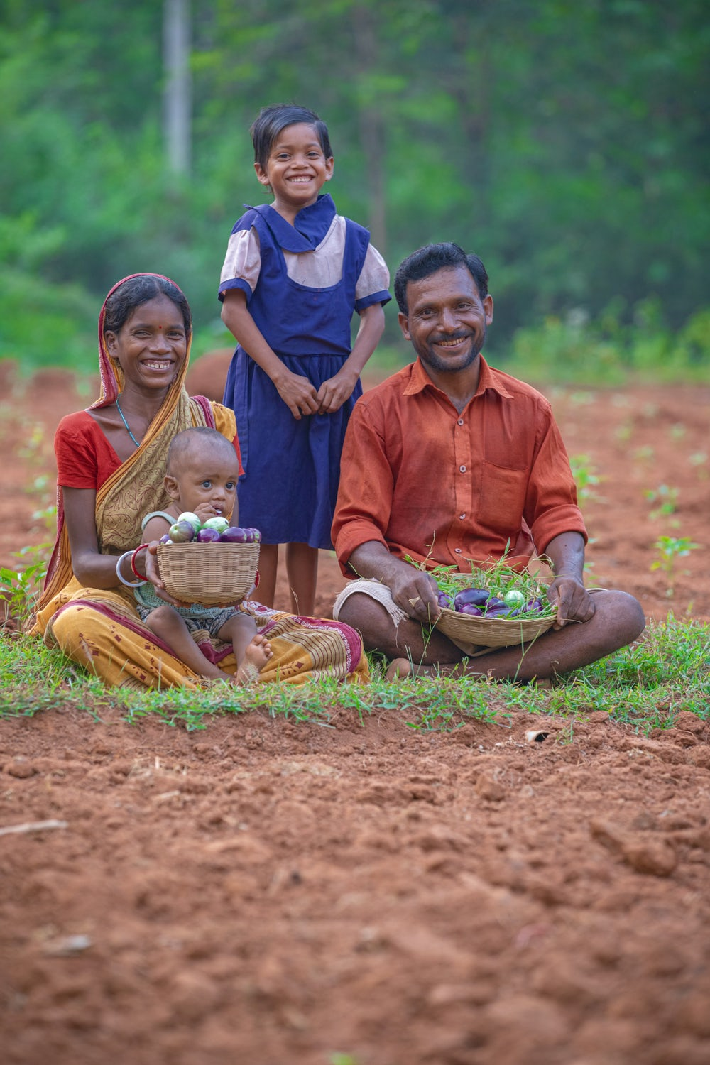 A family of four – a woman and man with a small baby and a toddler – sits on the group and smiles at the camera.