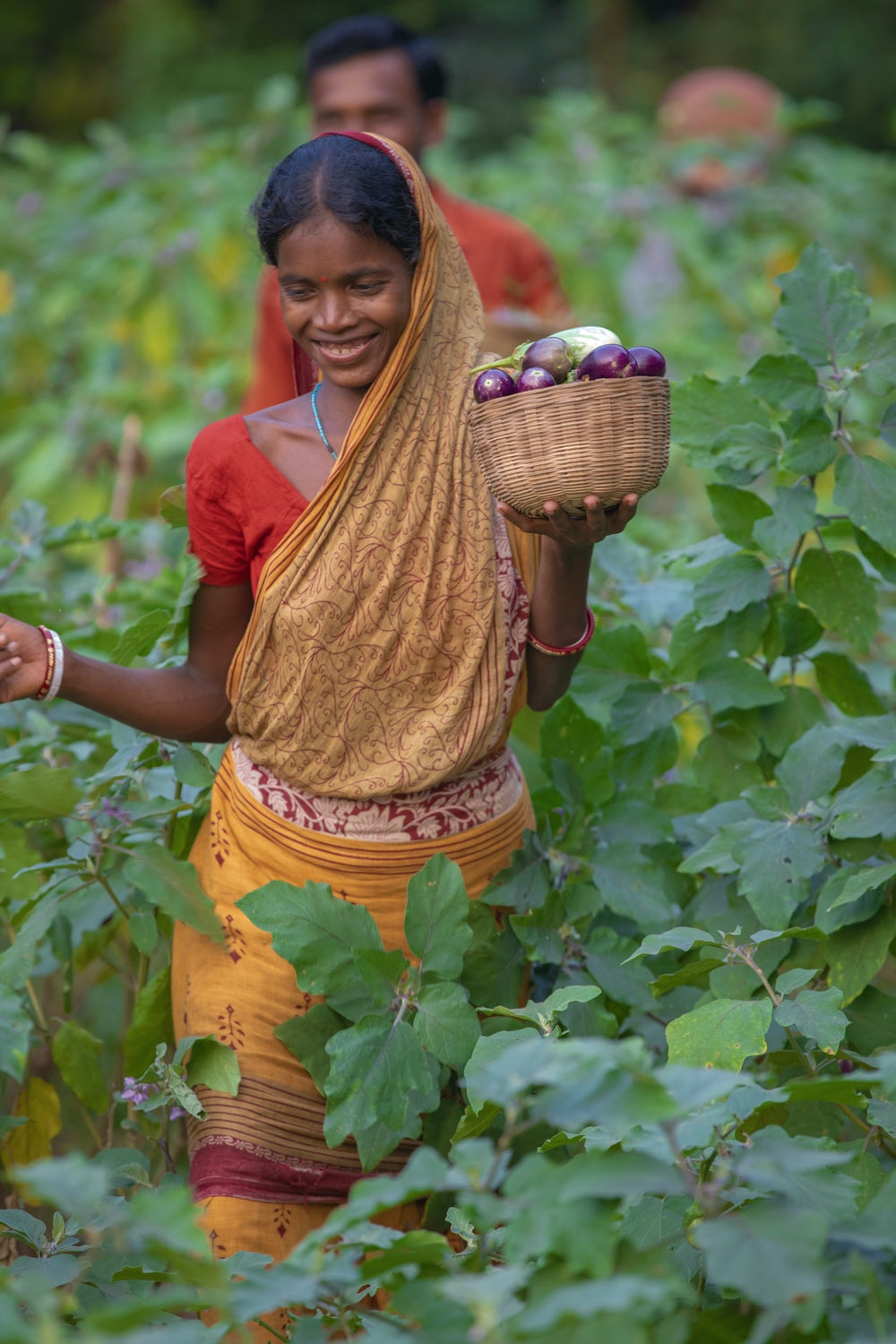 A smiling woman in India walks through her vegetable field.