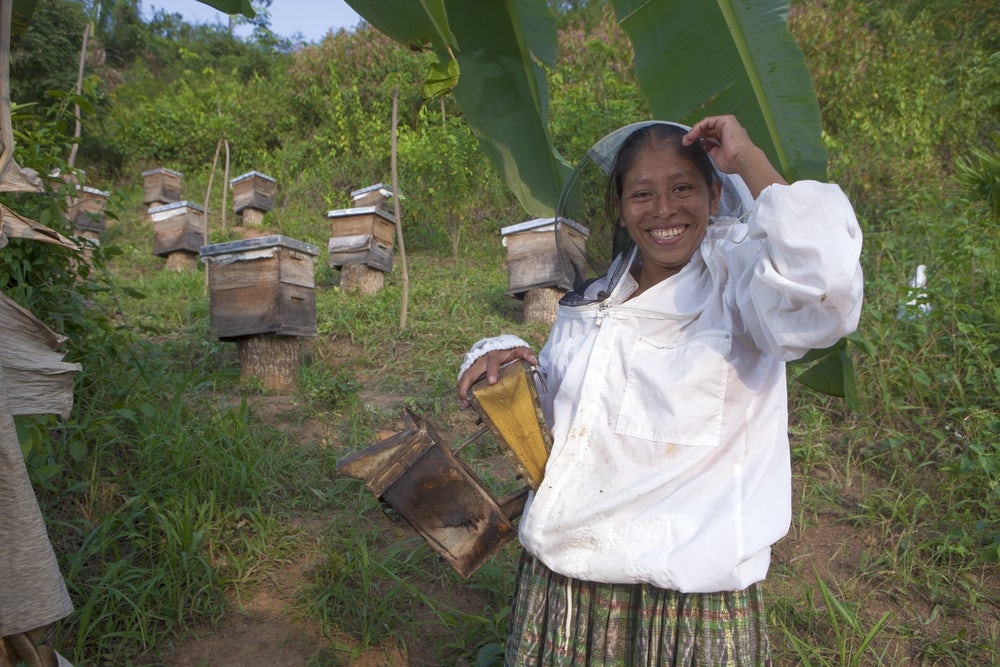A smiling Guatemalan woman in a bee suit poses with her beehivevs.