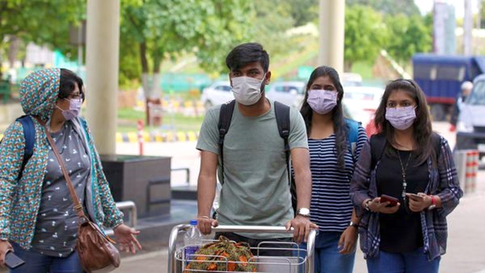 People at an airport wear protective masks.