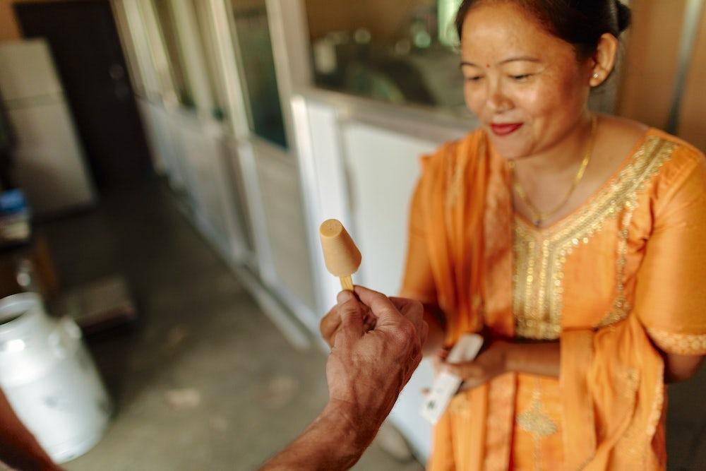 A nepali woman in bright orange kurta suruwal hands an ice cream to a customer off camera