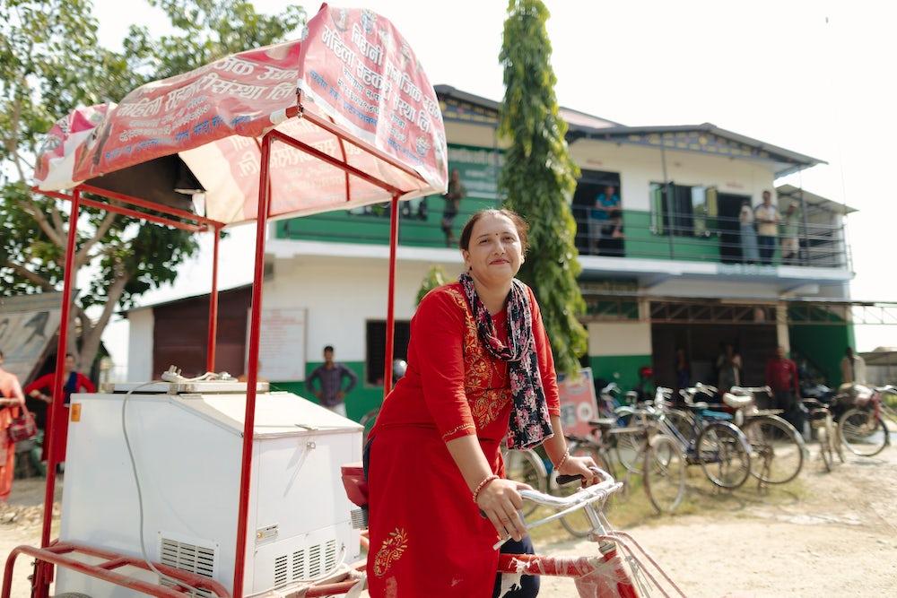 Mina Kandel rides the ice cream rickshaw outside the Bihani Cooperative in Kopawa, Nepal