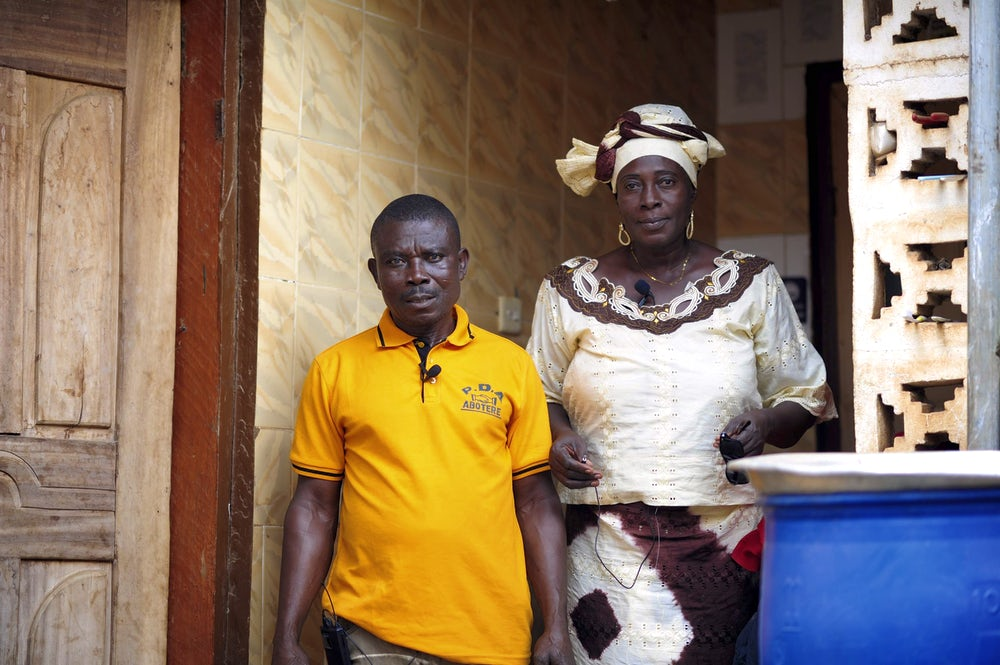 Rose stands beside her husband in the entryway of their home in Ghana