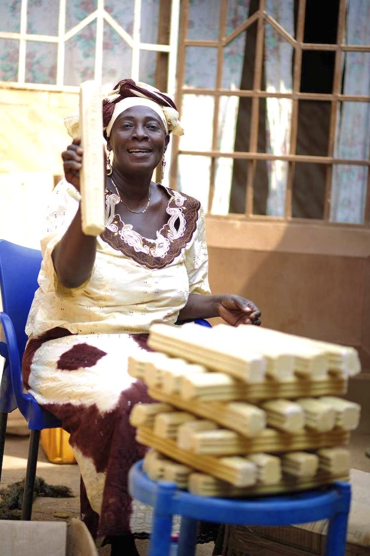 A sitting Ghanese woman proudly holds up a bar of soap she made for her growing business.