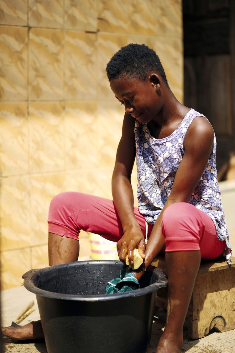 A Ghanese girl sits near a basin, washing her school uniform with the soap her mother made.