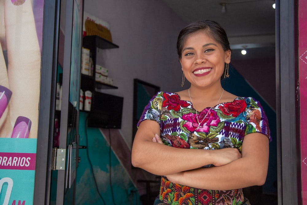 Nataly Mendoza Quieju stands at the entrance of her salon. Photo by Phil Davis.