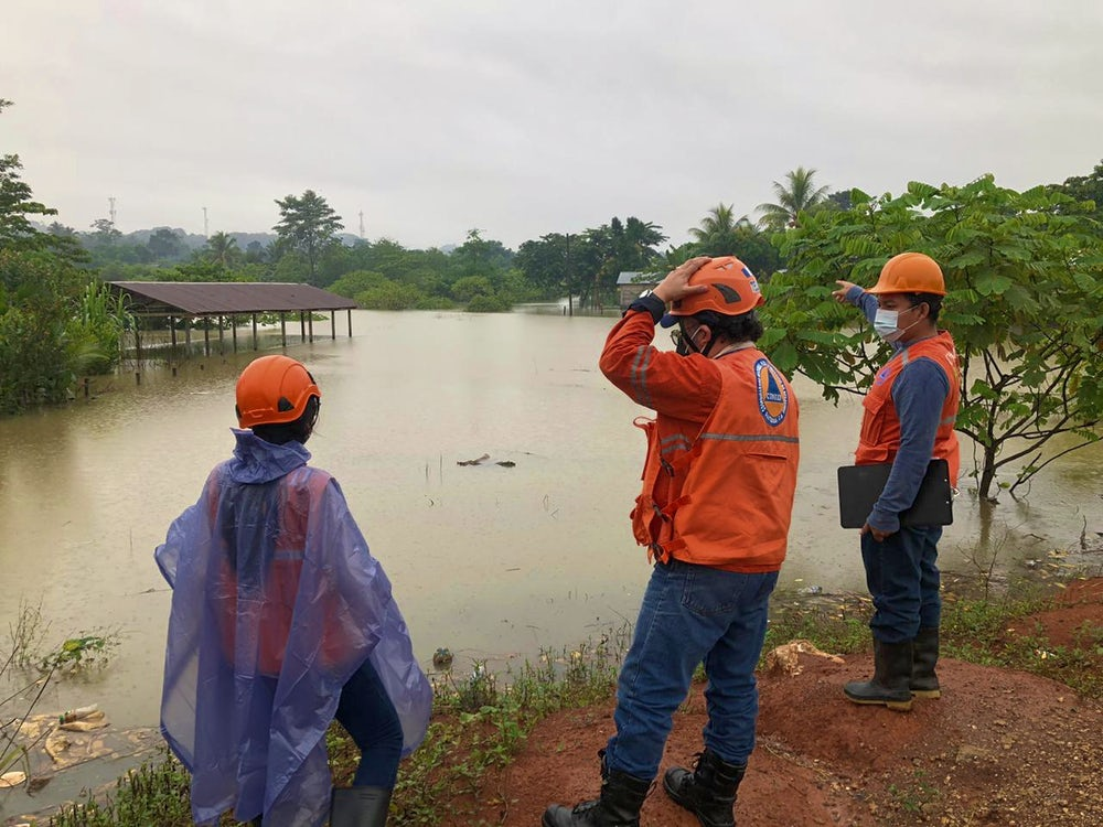 Emergency workers survey flooding in Chisec, Guatemala.