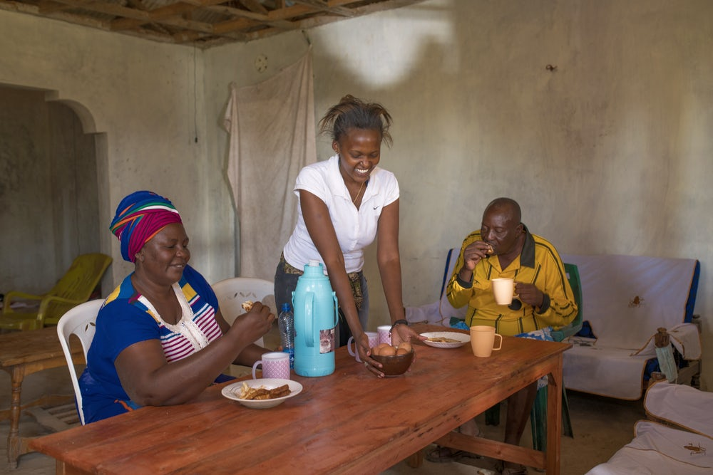 A woman, her daughter and her husband sit at a table eating eggs.
