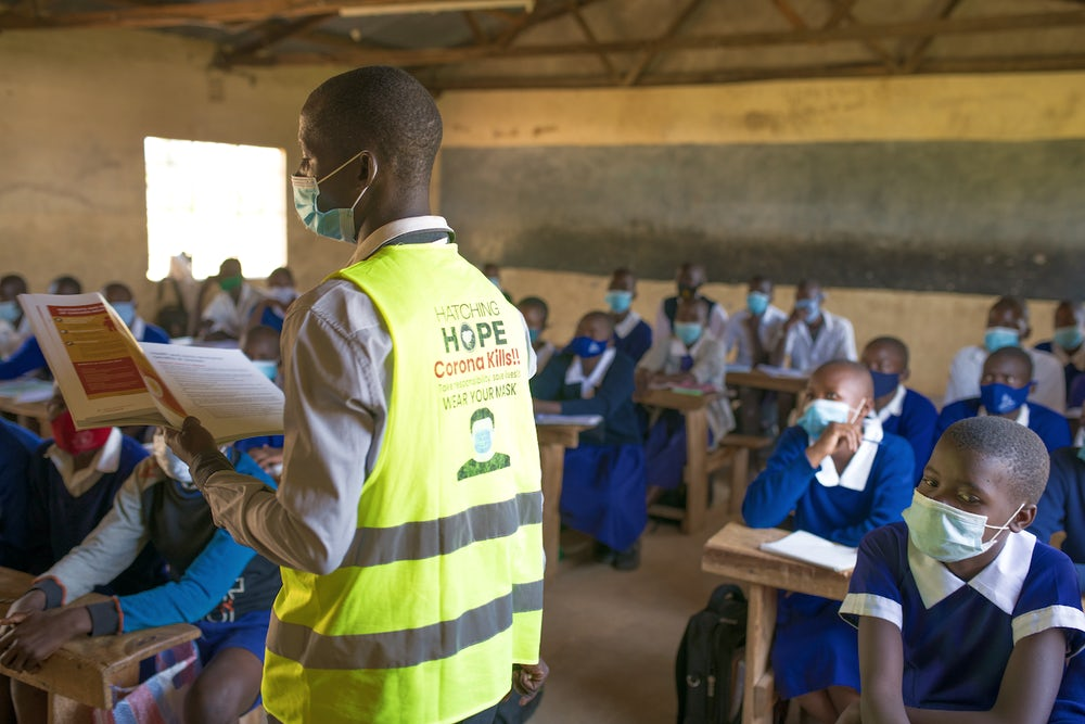 A man wearing a Hatching Hope vest teaches the benefits of eggs to a classroom of kids.