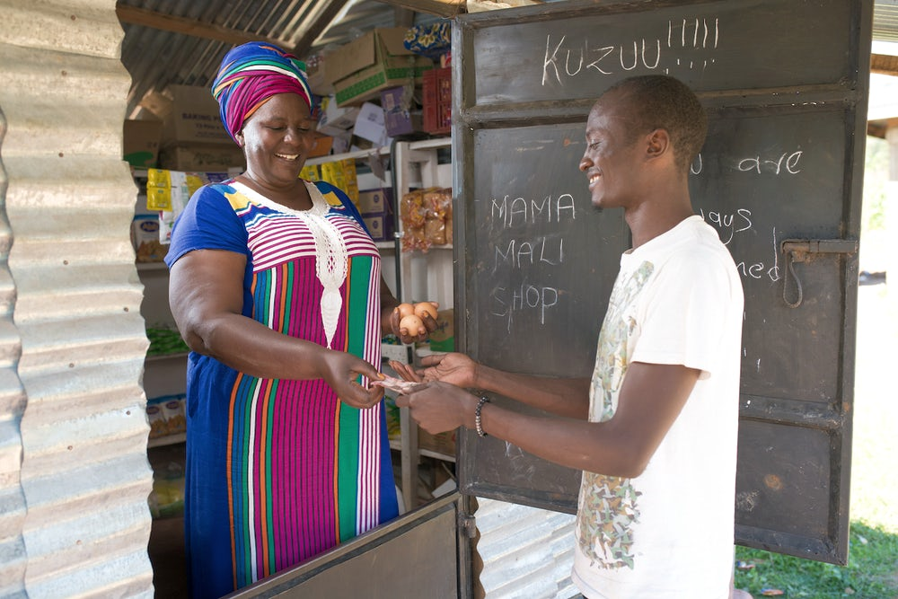 A woman wearing a vibrantly colored dress hands chicken eggs to a man at her shop.
