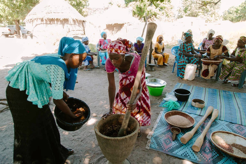 Grinding and preparing the nutrient-dense flour for their children is a social event. Photo by Lacey West.