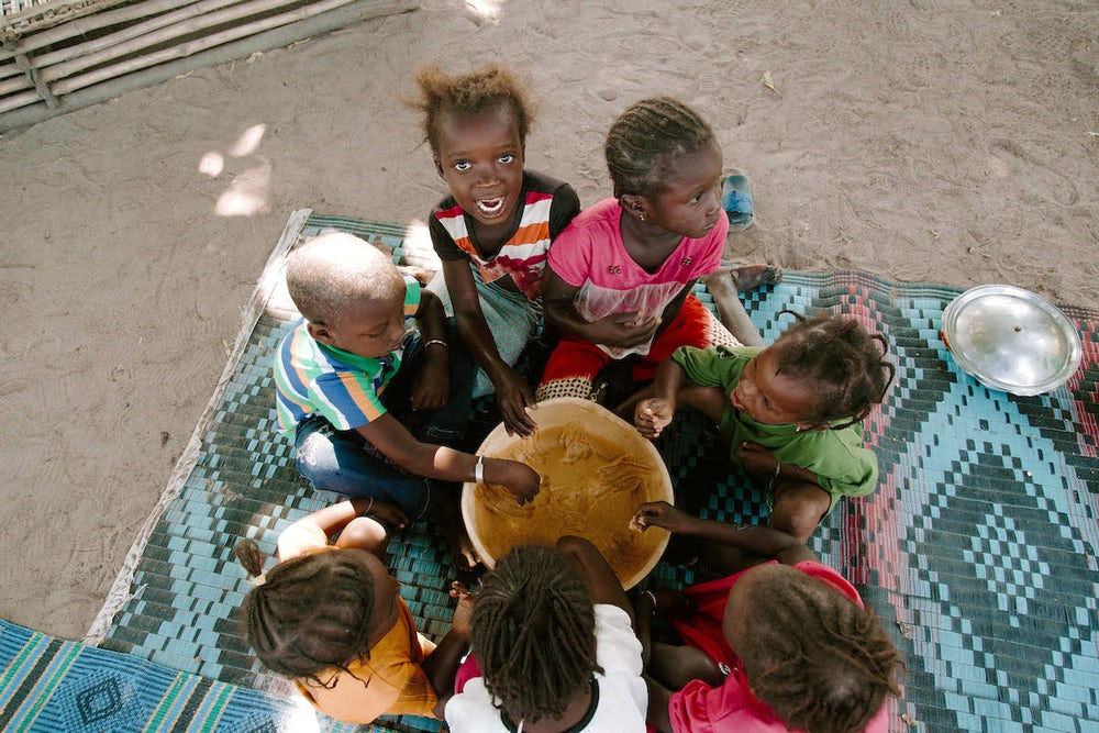 Children flock to eat a porridge specially formulated to provide good health and energy. Photo by Lacey West.