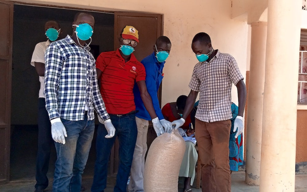A group of men gather around a bag of seeds. All are wearing blue masks in accordance to cdc guidelines.