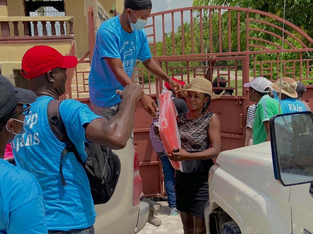 Heifer staff distribute tarps to Haiti residents.