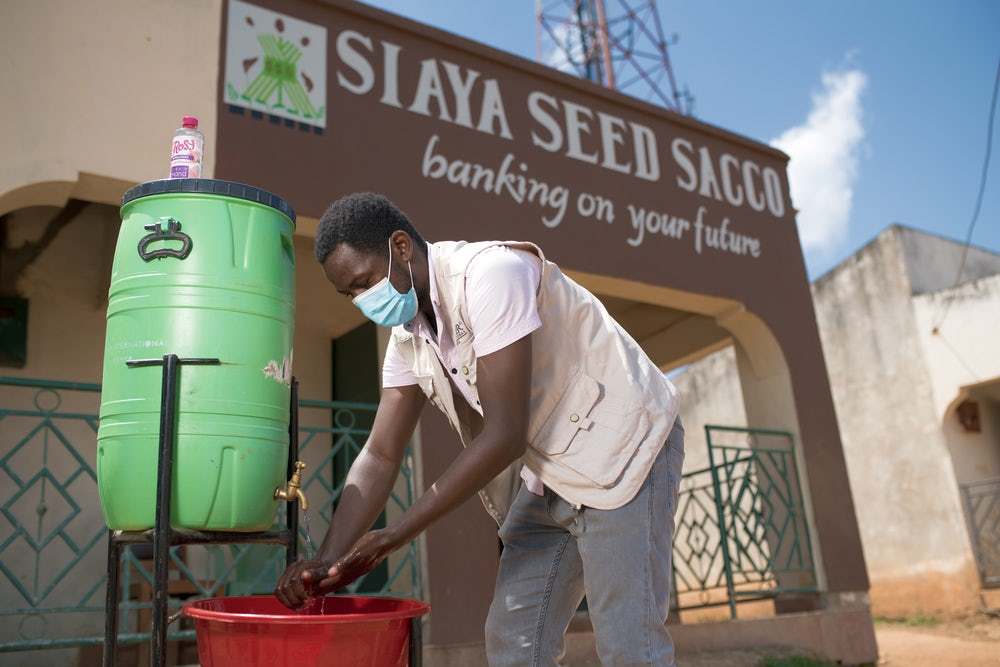 A Kenyan man washes his hands outside of a building with the words
