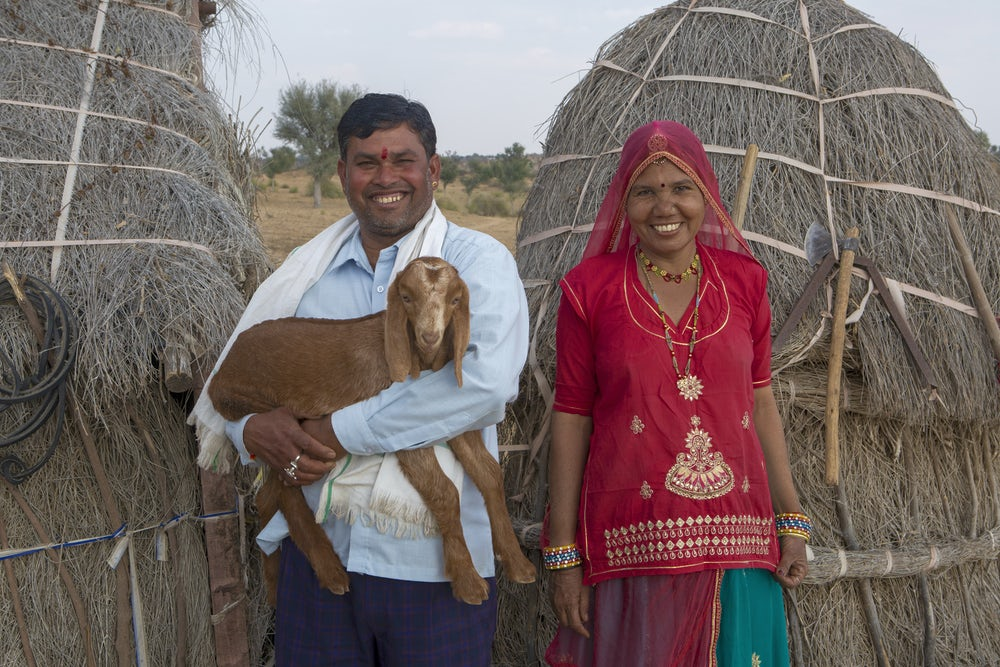An Indian couple stand together holding one of their goats.