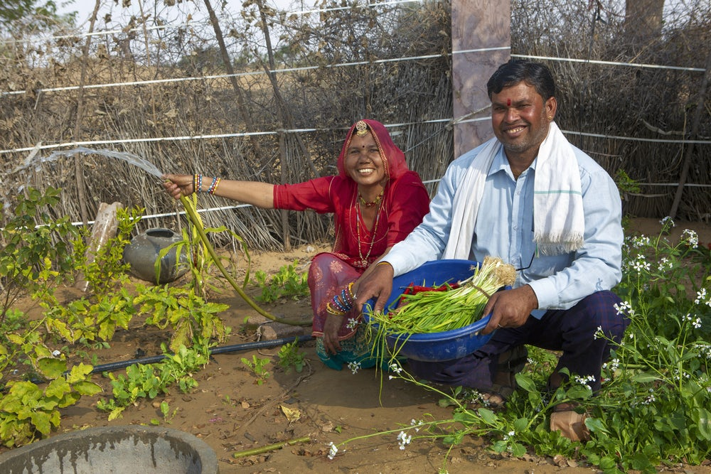 An Indian woman and man crouch down in their garden, smile at the camera and holding vegetables.
