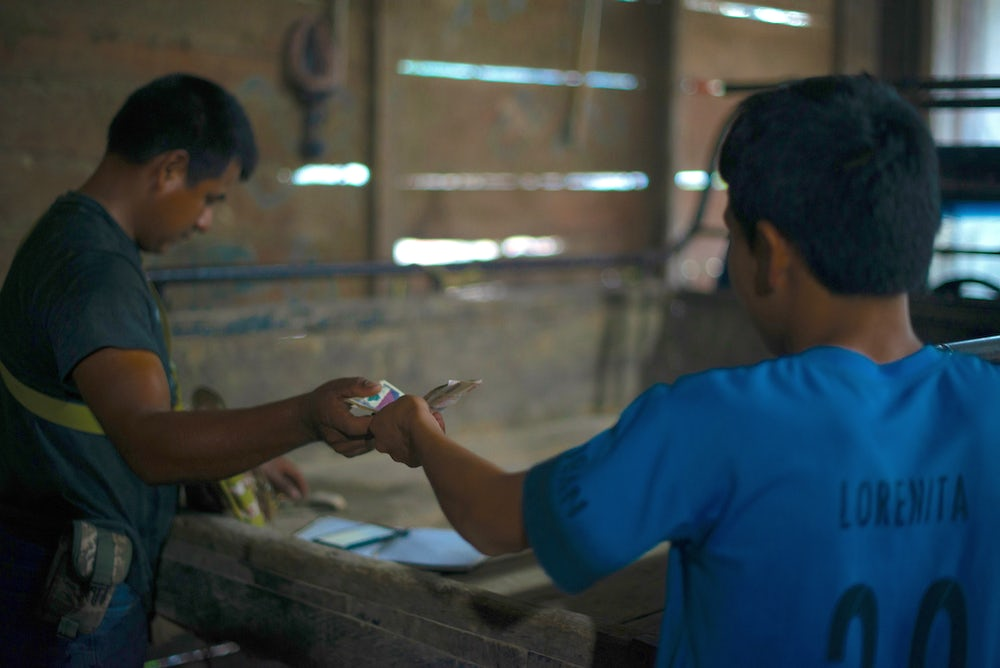 Two Guatemalan spice farmers exchange money.