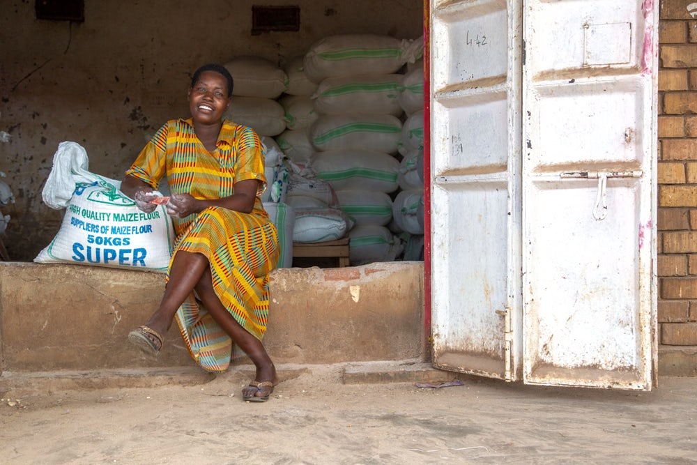A young woman sits in the doorway of her shop.