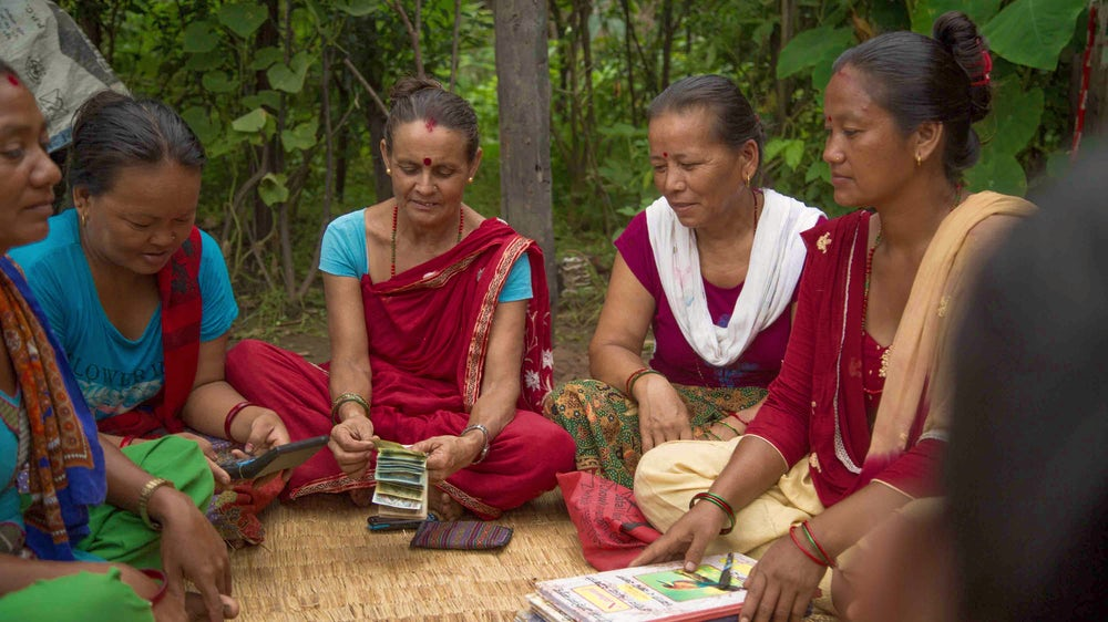 Members of the Sangam Women's Self-help Group in Nepal gather together discuss business and count their savings.