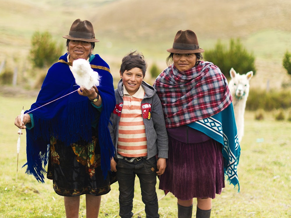 An alpaca sneaks in a family photo of María Juana Chaluisa (49), her nephew Michael (10) and her daughter Inés.
