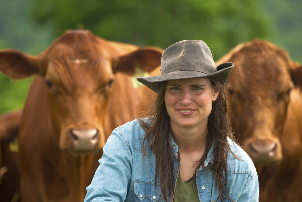 woman in front of herd of cows